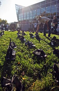 Combat boots line a grassy knoll near the bookstore, each pair representaing a California soldier who died in Iraq. ()