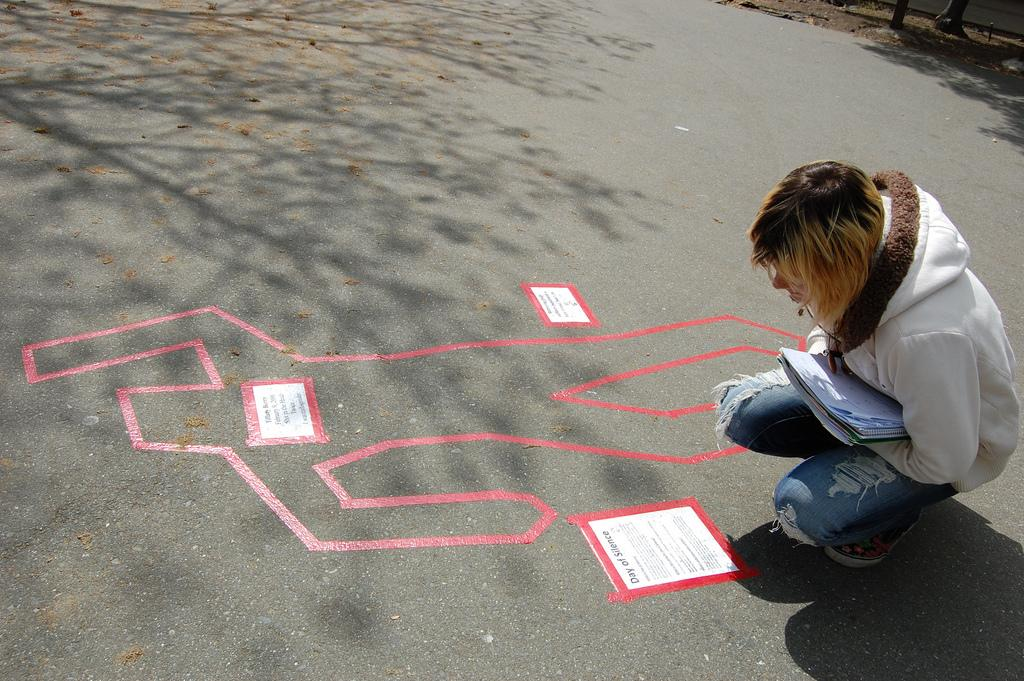 Student Lizbeth Brown looks over one of the body outlines across the campus which memorializes members of the LGBT community who were bullying victims on April 11. (Mariana Ramos / The Inquirer)