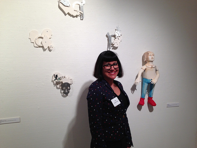 Edith Garcia, stands next to her work