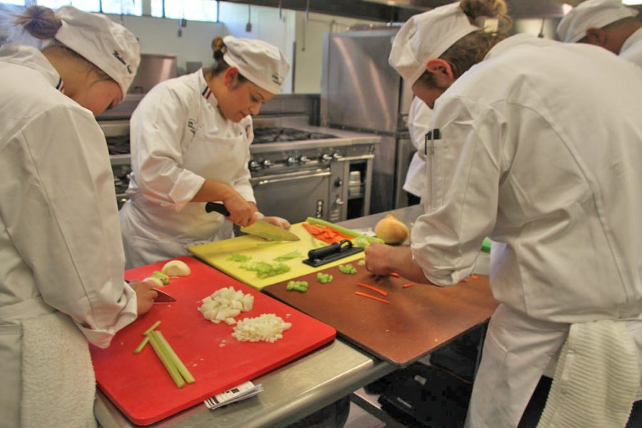 Baking and pastry majors Zach Matera, 22, Norine Wan, 27, and Madison August, 20 work away perfecting their various cuts and dices in the DVC culinary class.