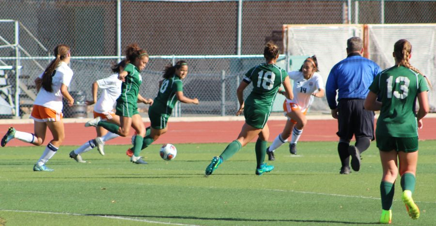 Karla Ramos kicking the ball with teammates Vanessa Ruvalcaba, Megan Melara and Chloe Lindemann playing against Cosumnes River College on the Vikings football field on Oct.18.