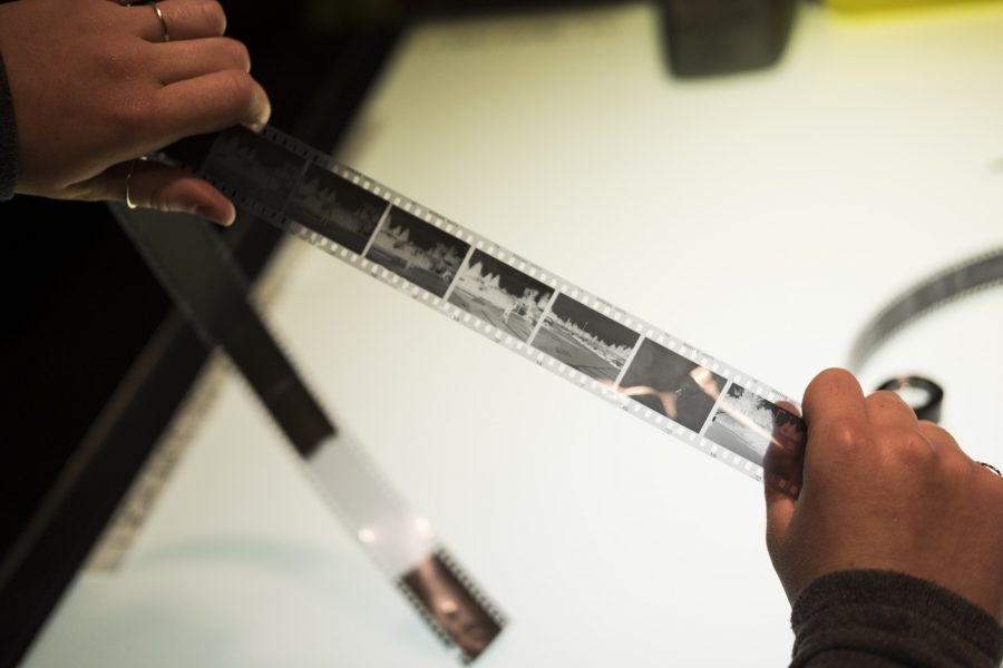 A student checks the exposure of their film shots using the table light.  Courtesy of Professor Nicole White