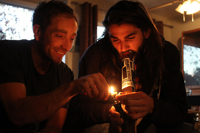 Two friends enjoy  cannabis using a water pipe, while assisting one another in their shared elation.