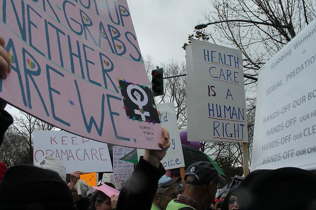 Participants hold up signs to show their solidarity during the Women's March in Walnut Creek, California on January 21, 2017.