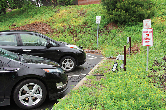 A Chevy Volt and Nissan Leaf charging in lot 4 at the only electric car outlet on campus.