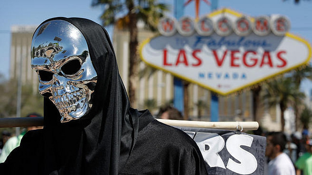 An Oakland Raiders fan stands in front of the sign welcoming visitors to Las Vegas. Photo courtesy of AP and csnbayarea.