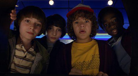 Noah Schnapp, FInn Wolfhard, Gaten Matarazzo, Caleb Mclaughlin staring at an arcade game