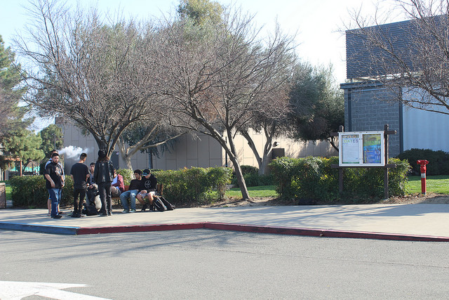 Students gathered around the unofficial DVC smoking spot in front of the Humanities/BFL building.