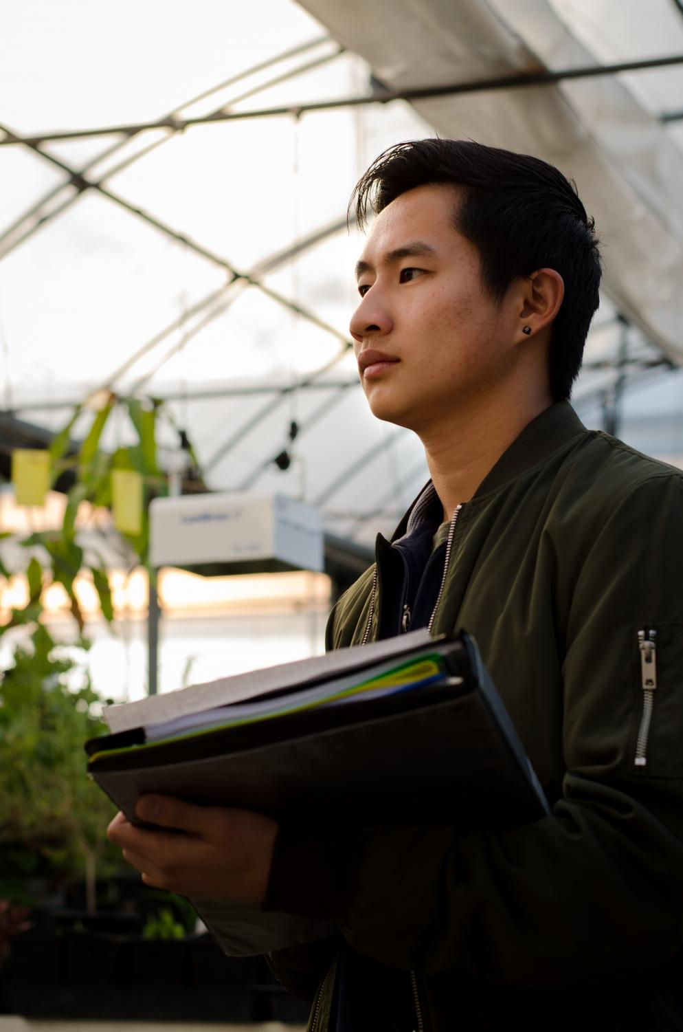Brandon Chan, engineering student, 22, creates a to do list for the Vertical Farming Club in a greenhouse at the DVC Horticulture area on Thursday, Feb. 23rd. He, and the rest of the club, are creating a sustainable vertical farming system to grow vegetables in layered beds.