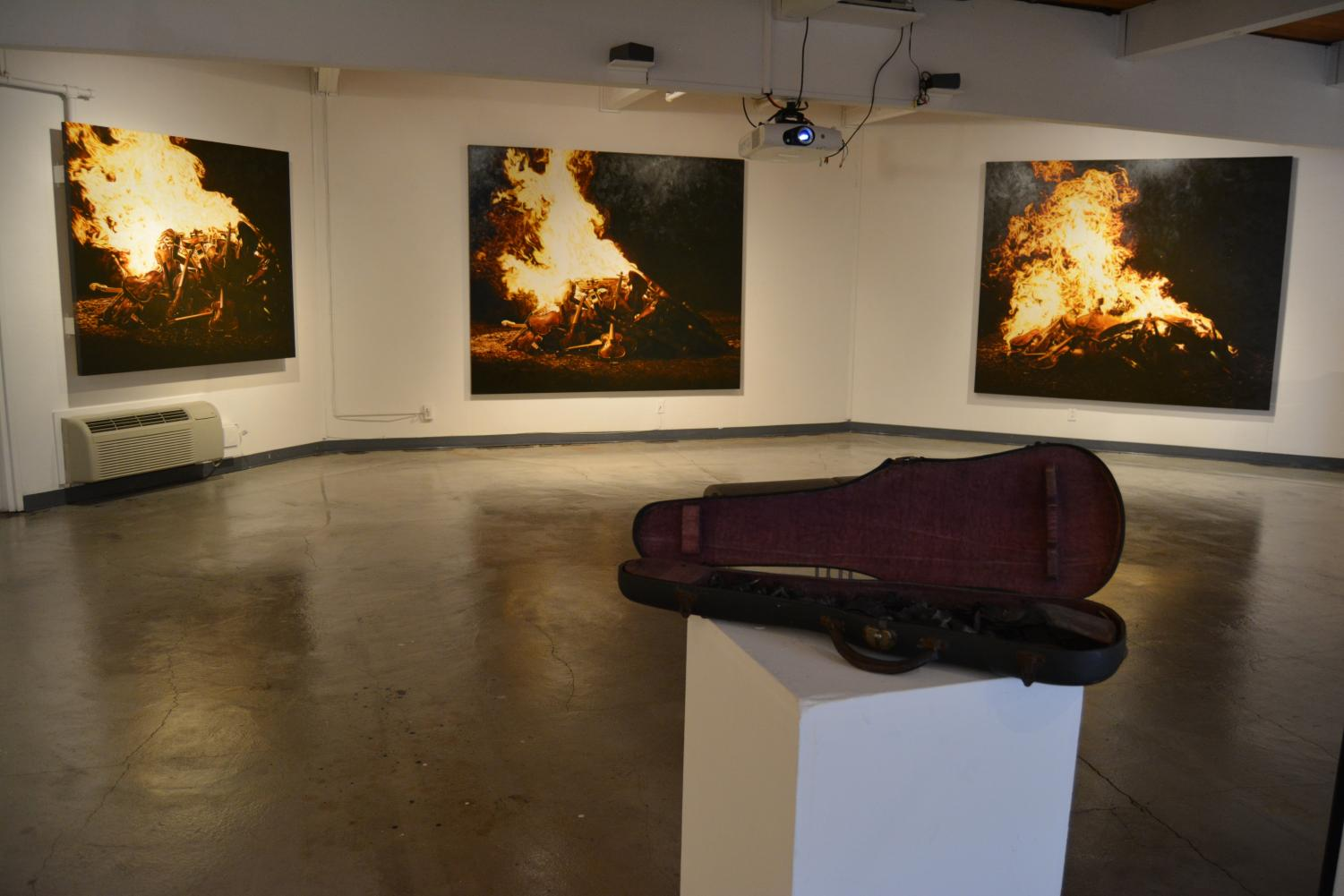 DVC art gallery showing paintings and burnt violin for art show at Pleasant Hill campus. (Samantha Laurey/The Inquirer).