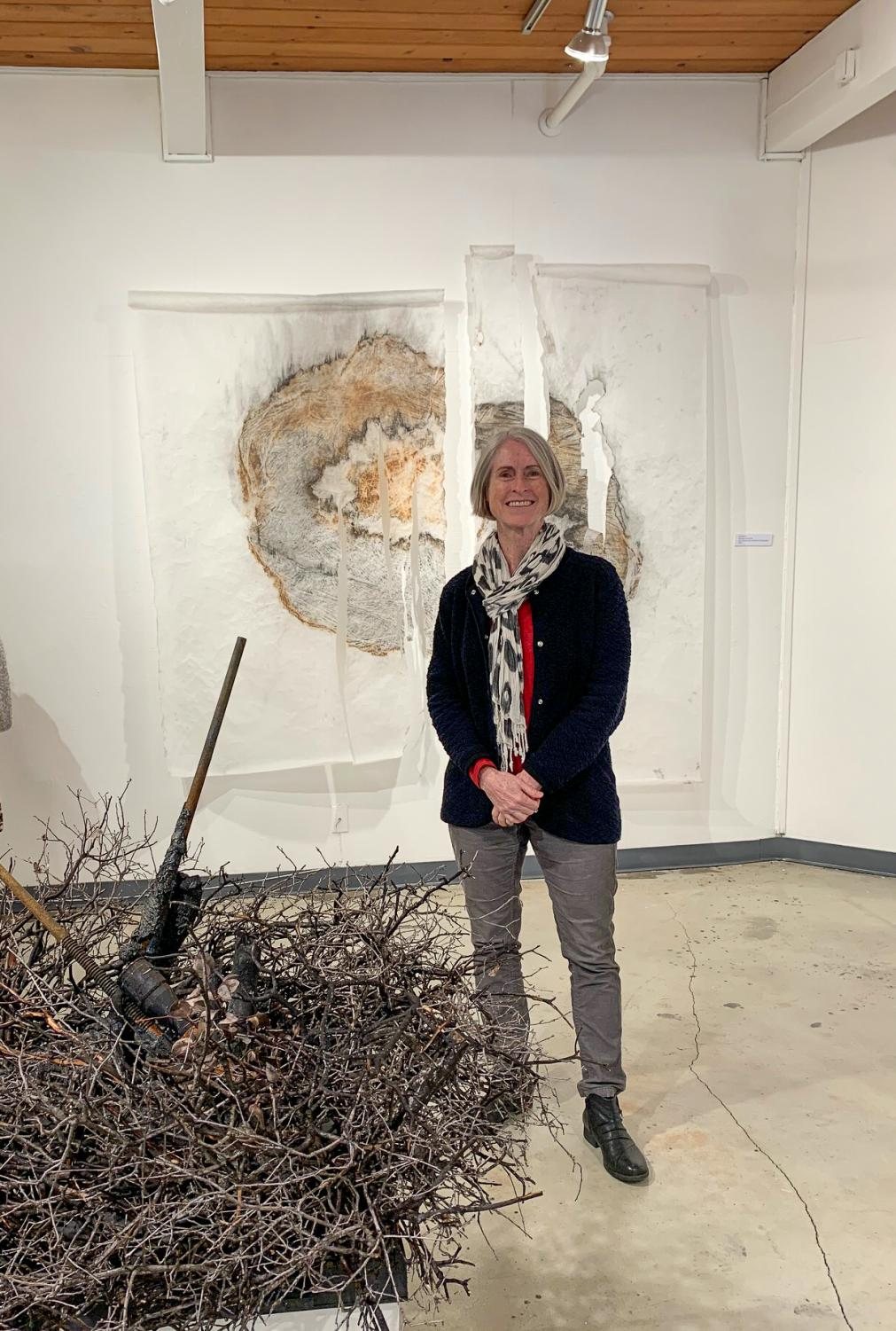 Eve Werner with two pieces of art she contributed to the gallery (Autumn Jarmel/The Inquirer).